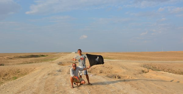 Showing our Drama of Llama team flag on the road we dared not ride.bad road in Kazakhstan