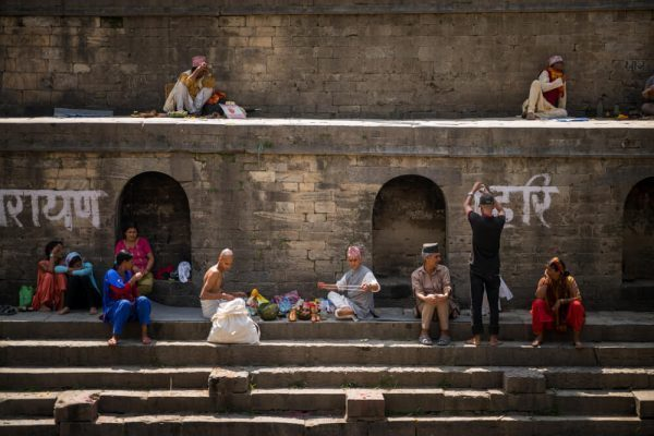 People sitting on the steps at Pashupatinath Temple