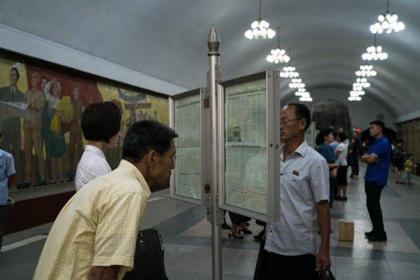 Reading the newspaper at the metro platform in Pyongyang, North Korea