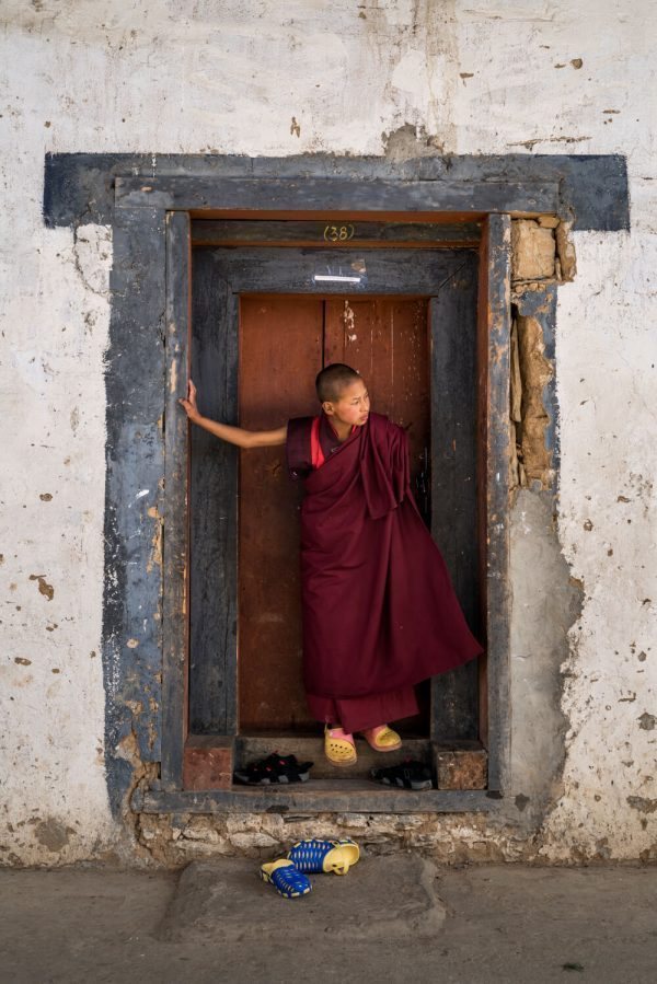 Monk on a doorway in Bhutan