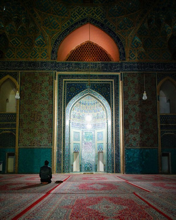 Man praying inside mosque in Yazd, Iran