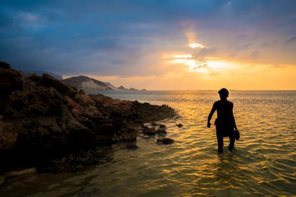 Abdullah walking on the beach in the sunset. Socotra